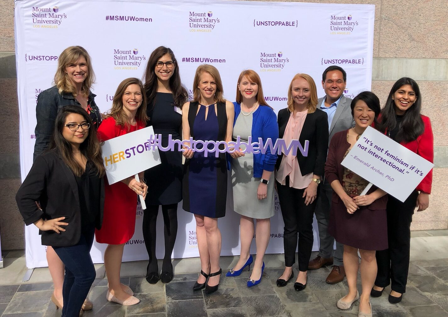 A photo of ten members of the Momentum team standing in front of a stand and repeat backdrop at the 2019 Report on the Status of Women and Girls in California