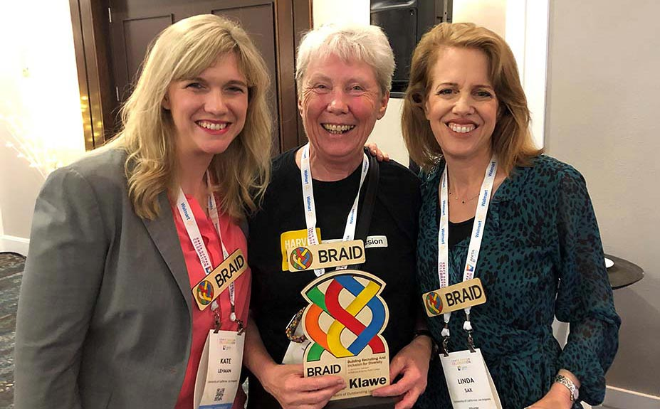 A photo of Dr. Kathleen Lehman (left) and Dr. Linda Sax (right) with BRAID co-founder, Dr. Maria Klawe (center) in front of a brown door inside of a room with white walls and a gray bulletin board.