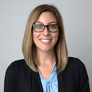 Katie is a white female with shoulder-length blonde hair and blue eyes. She is wearing glasses with black frames, a light blue top, and a black sweater. This photo of Katie was taken indoors with a white wall-background.