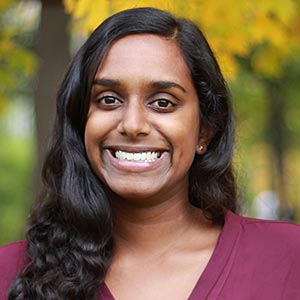 A close-up of Nadeeka, a South Asian woman with wavy hair slightly past her shoulder, smiling at the camera. She is wearing a burgundy shirt and there are trees with yellow leaves in the background.