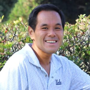 Chantra is a Southeast Asian man with medium tan skin, short black hair, and brown eyes. This photo of Chantra is a close-up portrait in front of a green leafy bush. Chantra is wearing a white polo with blue zig zag patterns with UCLA embroidered on the left side of the polo's chest.