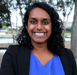Photo of a South Asian woman with black, curly hair at shoulder length wearing a bright blue shirt and black blazer.